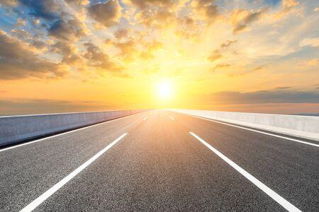 Carretera de asfalto recta y hermosas nubes al atardecer