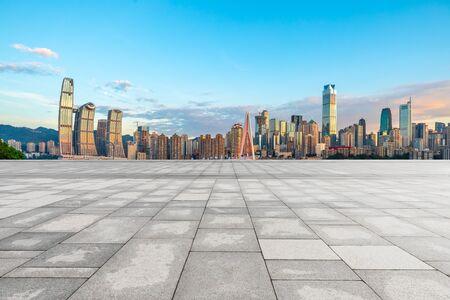 중국 충칭의 일몰에 건물이 있는 빈 광장 바닥과 도시 경관.