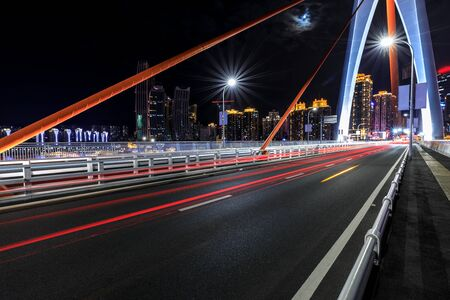 Urban road and bridge buildings pass through the financial district in Chongqing at night,China.