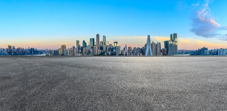 Empty race track ground and city financial district with buildings in Chongqing at sunrise,China.
