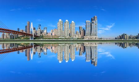 Edificios del distrito financiero de la ciudad moderna y reflejos en el agua, Chongqing, China.
