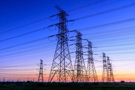 Hoogspanning elektriciteit toren hemel zonsondergang landschap, industriële achtergrond.