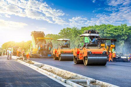 Baustelle legt neue Asphaltstraßenpflaster, Straßenbauarbeiter und Straßenbaumaschinenszene.
