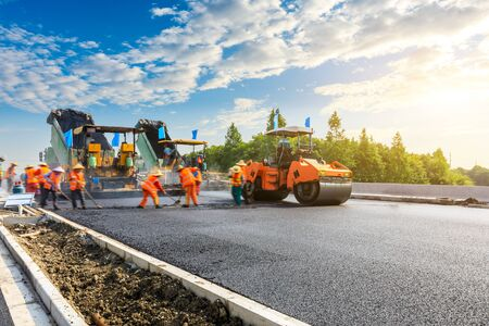 El sitio de construcción está colocando nuevo pavimento de asfalto, trabajadores de la construcción de carreteras y escena de maquinaria de construcción de carreteras.