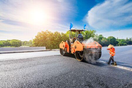 El sitio de construcción está colocando nuevo pavimento de asfalto, trabajadores de la construcción de carreteras y escena de maquinaria de construcción de carreteras. Foto de archivo