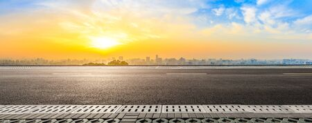 Empty asphalt road and city skyline at sunrise in Hangzhou, China.