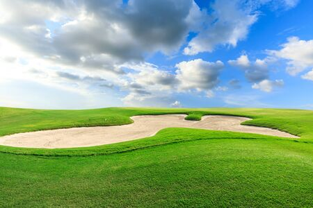 Green golf course and blue sky with white clouds.
