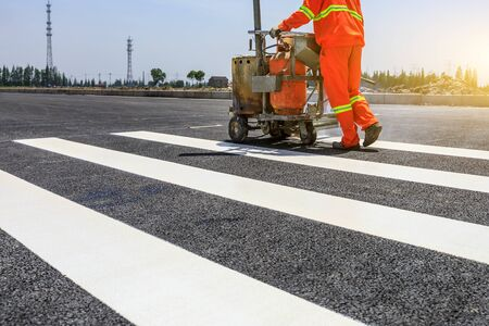Road workers use hot-melt scribing machines to painting pedestrian crosswalk on asphalt road surface in the city.