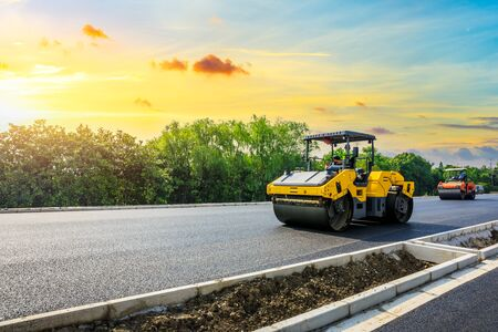 Construction machinery and workers laying new asphalt road pavement Stockfoto