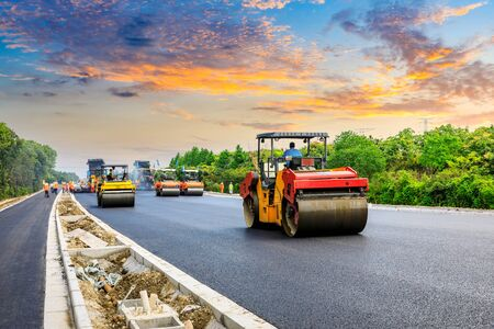 construction machinery and workers laying new asphalt road pavement