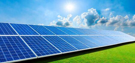 Panneaux solaires photovoltaïques et herbe verte sur fond de ciel, concept d'énergie alternative propre et verte.