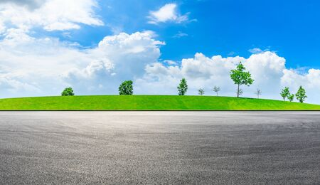Empty race track and green grass with tree under the blue sky.