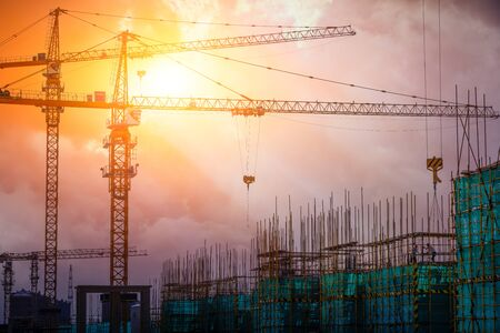 Tower crane and building construction site silhouette at sunrise. Banque d'images