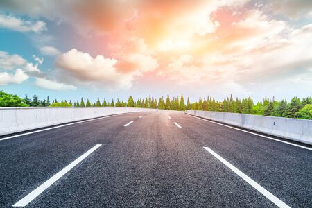 Asphalt road and forest with sky cloud landscape.Highway road background. Фото со стока