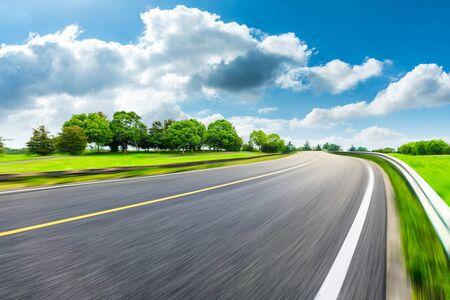 Fast moving asphalt road and green forest landscape. Zdjęcie Seryjne