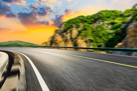 Motion blurred road and mountains at sunrise.mountain road background. Stockfoto