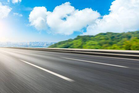 Route asphaltée floue de mouvement et montagne verte avec les toits de la ville de Hangzhou. Banque d'images
