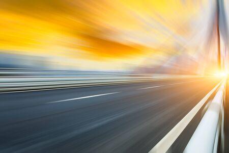 Fast moving asphalt road and bridge background.