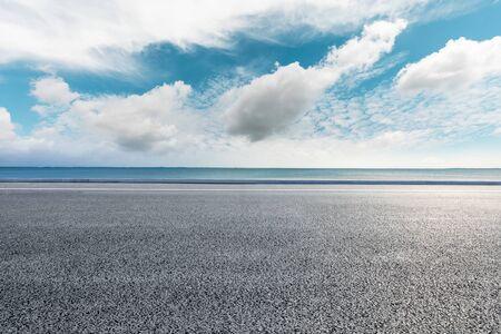 Empty asphalt road and lake under blue sky.