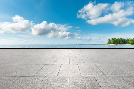 Empty square floor and lake with tree under blue sky.