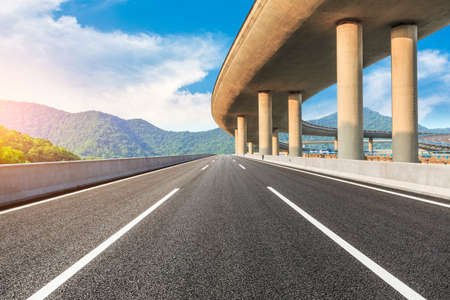 Asphalt road and viaduct with mountain landscape.