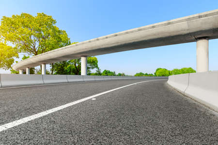 Asphalt road and viaduct with green tree on a sunny day.