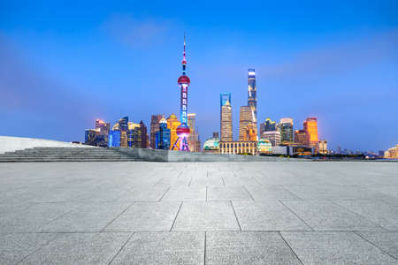 Empty square floor and city skyline and buildings at night in Shanghai,China.