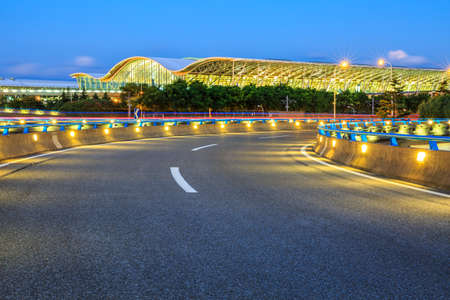 Asphalt road and airport buildings at night in Shanghai,China.