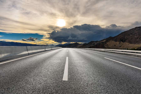 Asphalt road and mountain with sky clouds landscape at sunrise.