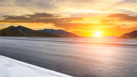 Motion blurred asphalt road and mountain landscape at sunrise. Stock fotó