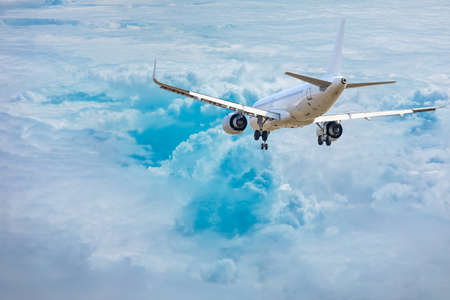 Commercial airplane flying above blue sky and white clouds. Stock Photo