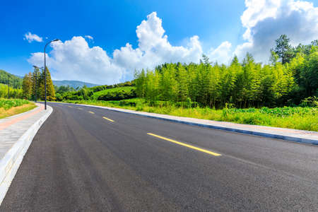 Asphalt road and green plants with mountain natural scenery in Hangzhou on a sunny day.