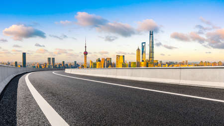 Empty asphalt road and Shanghai skyline with buildings at sunset.