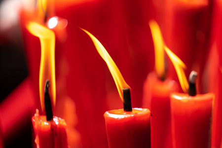 Rows of burning red candles are used in religious prayers