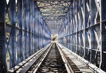 Blue metal bridge on the railroad tracks photo