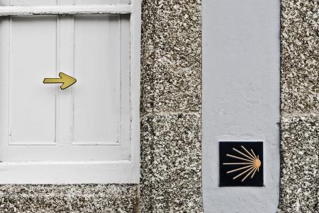 camino: Directional Sign of the Camino de Santiago in the facade of a building