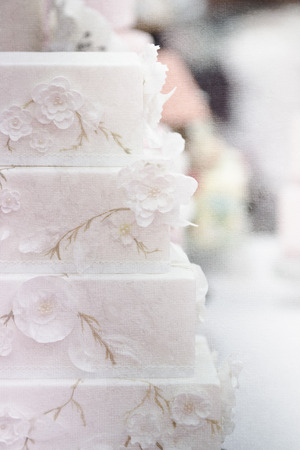 A white wedding cake with pink rose petals. photo