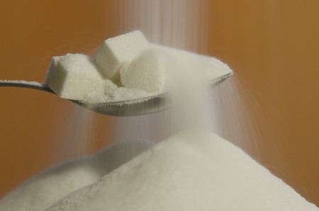 definite: Heap of sugar and pouring more from a spoon Stock Photo