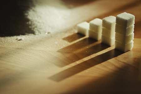 definite: Concept: Ascending stacks of sugar cubes on wooden table with natural light.
