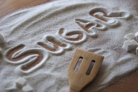 definite: Inscription sugar made into pile of white granulated sugar