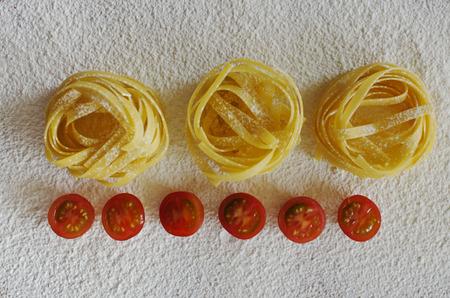 definite: Raw ribbon pasta with tomatoes on flour.