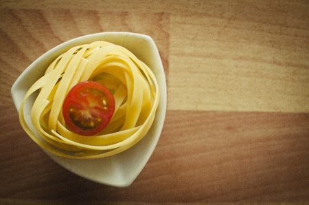 definite: Raw pasta on the wooden table.