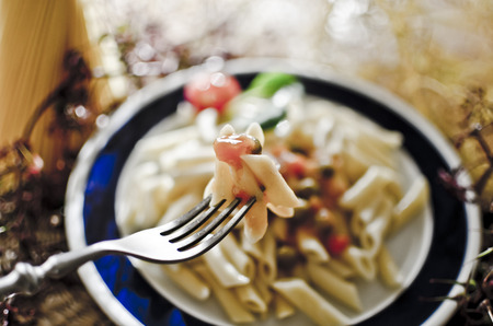 definite: Pasta on fork with sauce and parsley Stock Photo