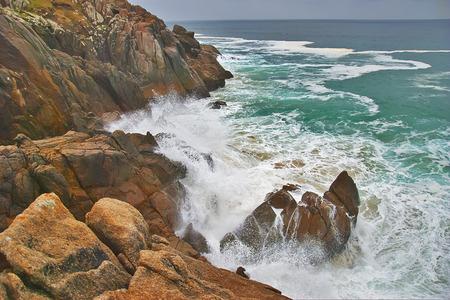 definite: wave crashes on to dangerous rocks.
