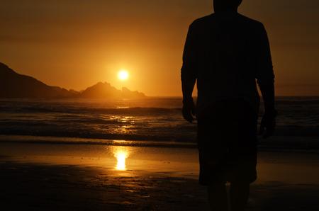 hombre solitario: solitario hombre que camina a la puesta de sol