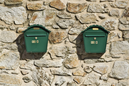 definite: Two ordinary post boxes on the stone wall
