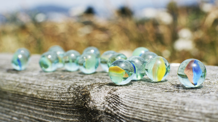 definite: Glass marbles on wood.