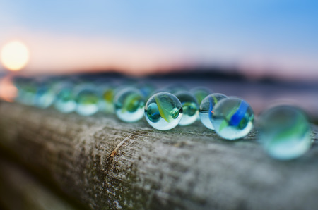 definite: Glass marbles at sunset.