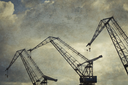industry moody: Harbor cranes silhouettes at sunset with texture. Stock Photo