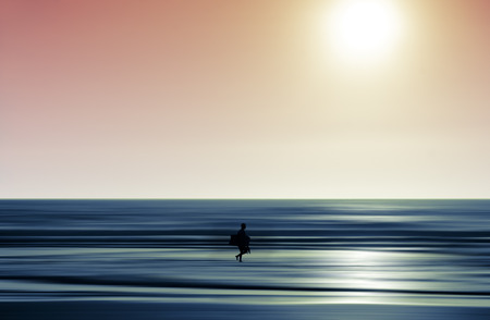 definite: surfer walking into the abstract waves at sunset. Stock Photo